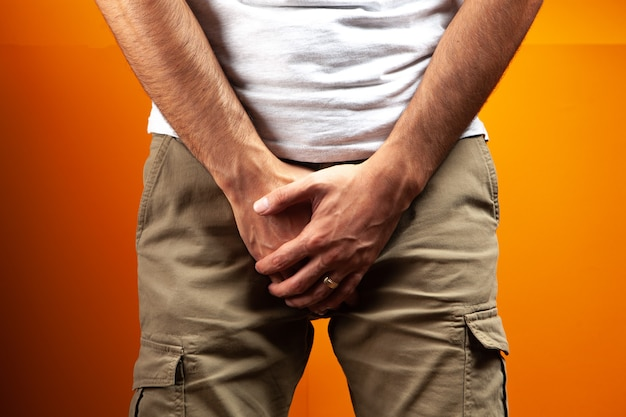 Man covered his groin on an orange background