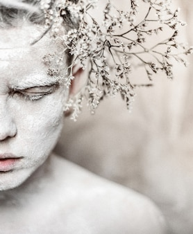 Man covered with white paint and branch behind his ear