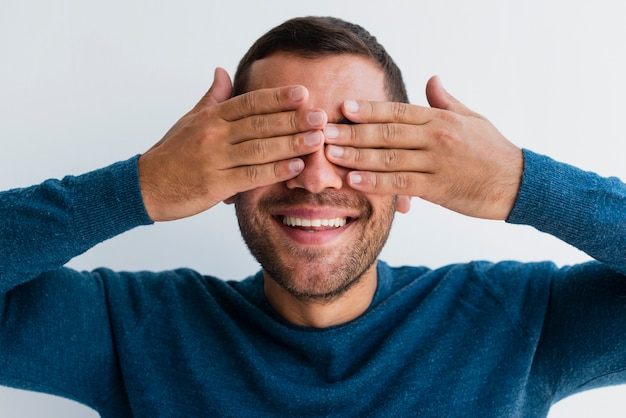 Man covering both eyes with hands