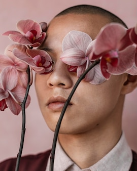 Man covering eyes with flowers