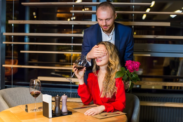 Man covering eyes of woman with hand in restaurant