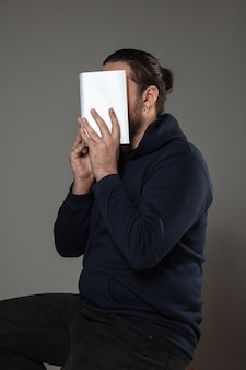 Man covering face with book while reading on grey wall