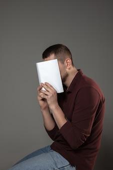 灰色の壁で読んでいる間、本で顔を覆っている男。祝う、教育、芸術、新しいキャラクターのコンセプトを楽しむ。