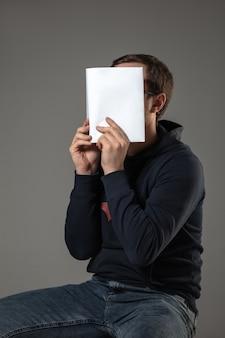 Человек закрывает лицо книгой во время чтения на серой стене