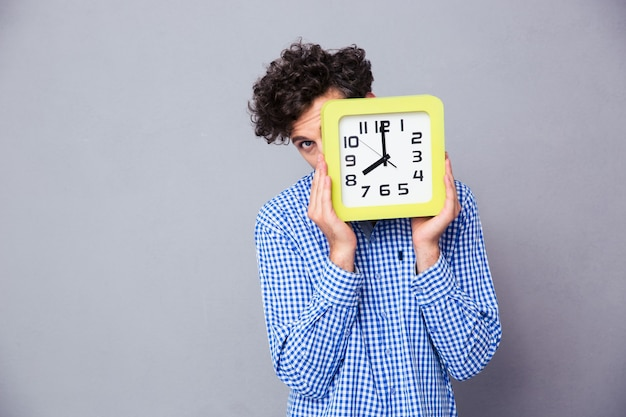Man covering face with clock and looking to the front