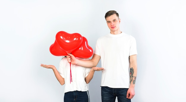Man covering face of woman with heart balloons