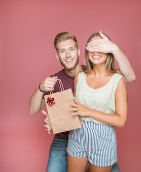 Man covering her girlfriends eyes while giving gift shopping bag