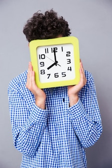 Man covering his face with big clock