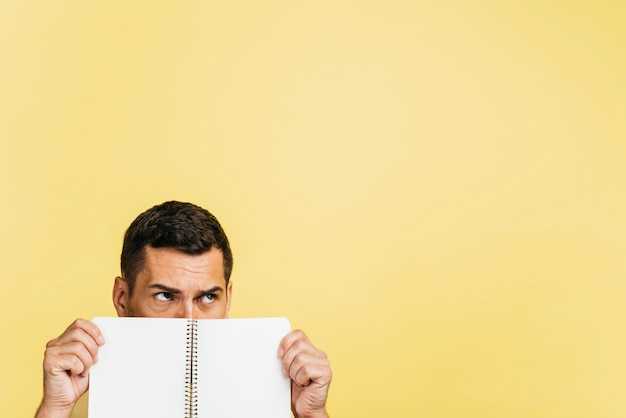 Man covering his face with an empty notebook