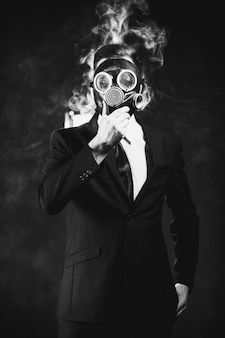 Man covering his face with a gas mask surrounded by nicotine fumes. danger of being passive smoker concept