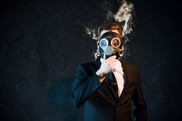Man covering his face with a gas mask surrounded by nicotine smoke. danger of being passive smoker concept