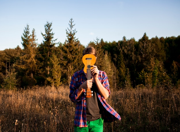 Man covering his face with ukulele guitar