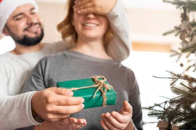 Man covering his wife's eyes for a christmas gift at home