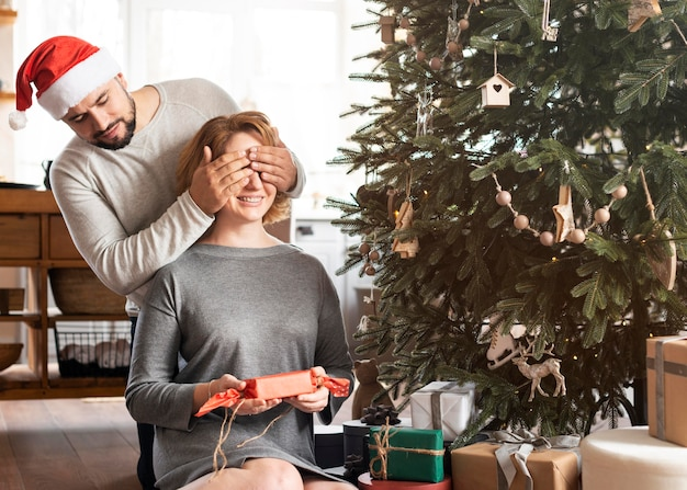Man covering his wife's eyes for a christmas gift