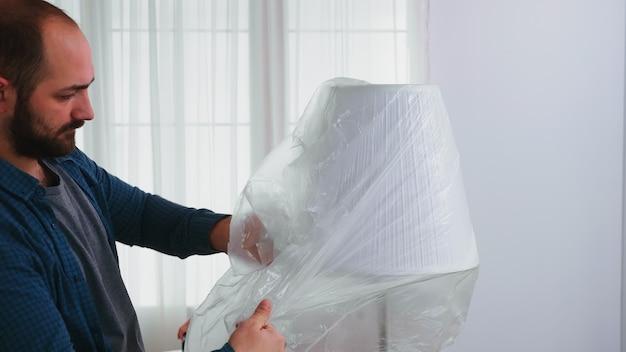 家のリフォームの前にプラスチックシートでランプを覆う男。リフォームと改善中のアパートの改装と住宅建設。修理と装飾。