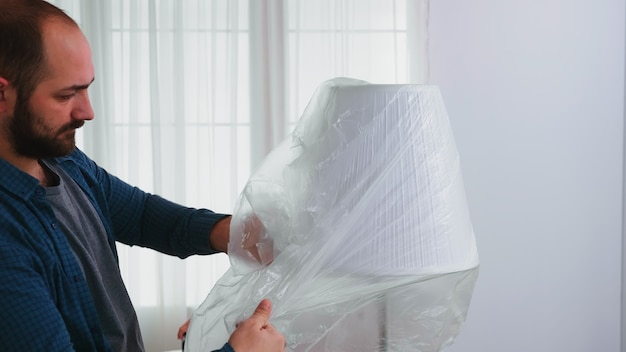 Man covering lamp with plastic sheet before home renovating. apartment redecoration and home construction while renovating and improving. repair and decorating.