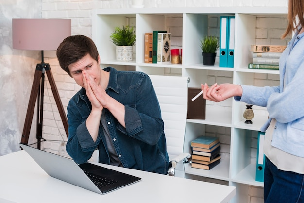 Man covering nose while his colleagues smoking in office