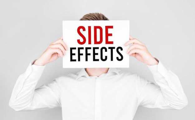 Человек закрывает лицо белой бумагой с текстовыми побочными эффектами