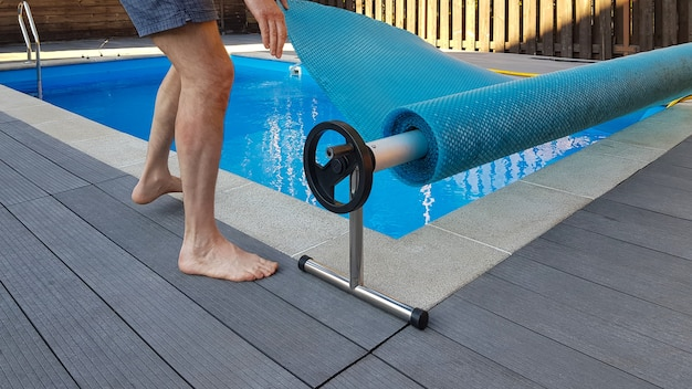 男は保護のためのカバーでプールをカバーします