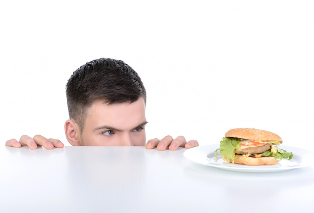 A man crawls out from under table and looks at hamburger.