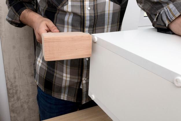 Человек создает шкаф из дерева среднего размера