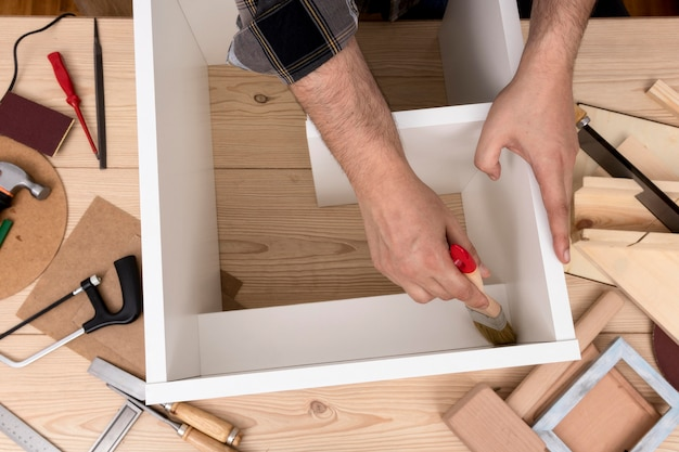 Man creating a cabinet from wood top view