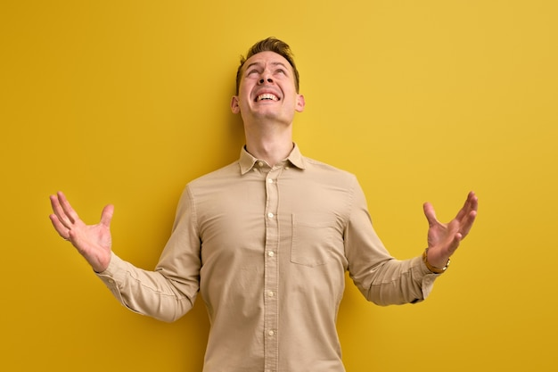 Man cries and screams, gesticulating with hands isolated on yellow wall