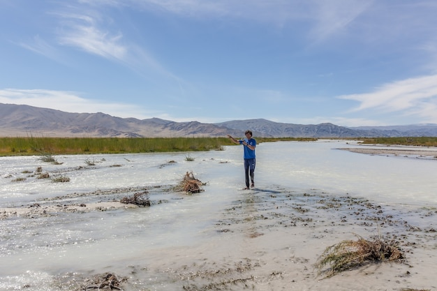 Man crosses a white mountain river on foot. altai, mongolia.