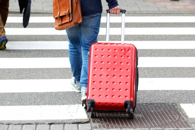 Man crossing the street with suitcase