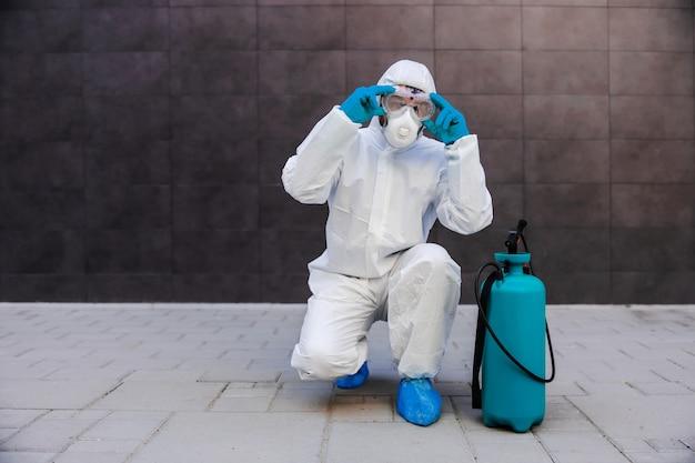 屋外でしゃがみ、顔にマスクを置く男。コロナウイルスの概念を広める予防。