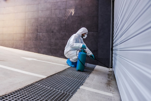 Man crouching and spraying with disinfectant garage door to prevent spreading corona virus