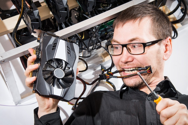 Man cryptocurrency miner connecting new graphics card to mining farm. it equipment.