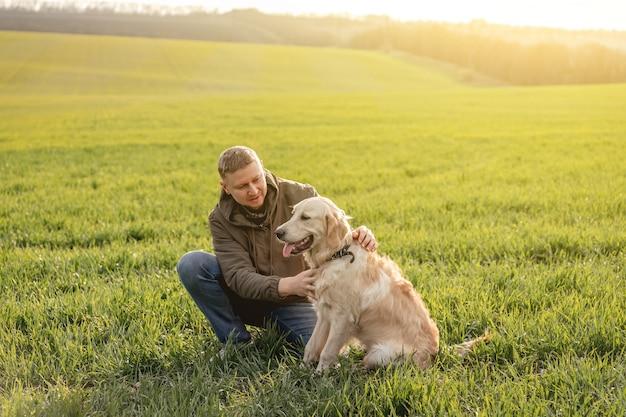 Человек обнимает собаку на поле