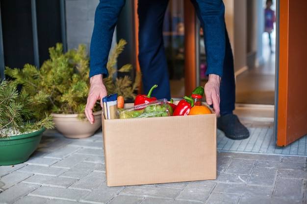 Man customer accepting box with food. delivery at home