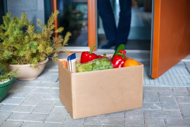 食品の箱を受け入れる男性の顧客。配達