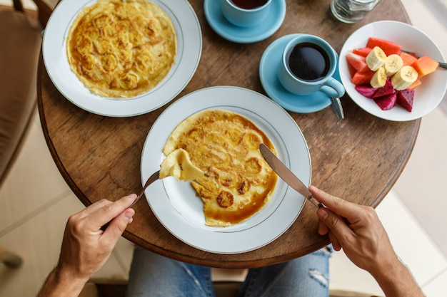 Man cuts banana pancakes breakfast in a hotel on bali