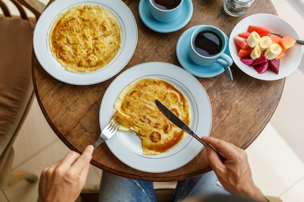 Man cuts banana pancakes breakfast