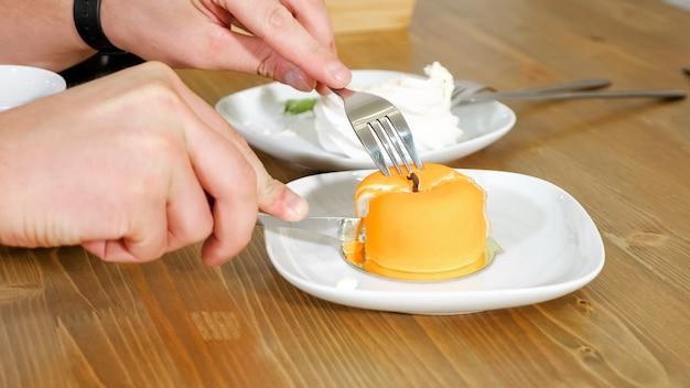 男は甘い店の極端なクローズビューの木製のテーブルで白いプレートにナイフで美しい黄色いリンゴの形をしたケーキをカットします