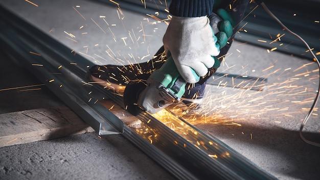 Мужчина режет металлический профиль болгаркой. промышленная концепция