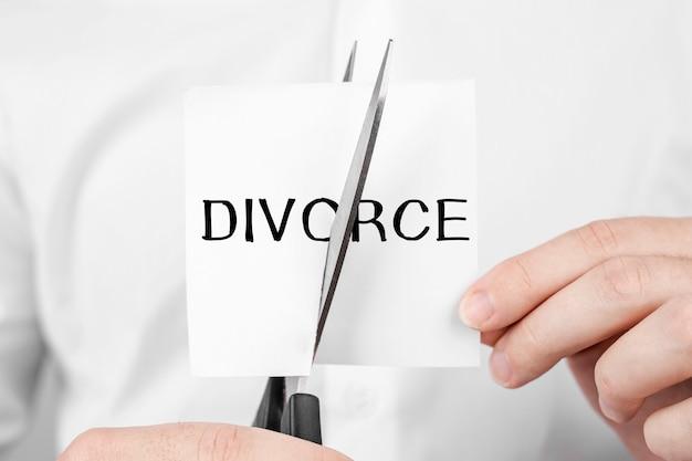 Мужчина режет ножницы наклейку с текстом развода