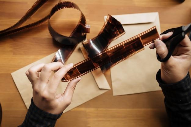 男はヴィンテージフィルムを35mmカットします。水平。上面図