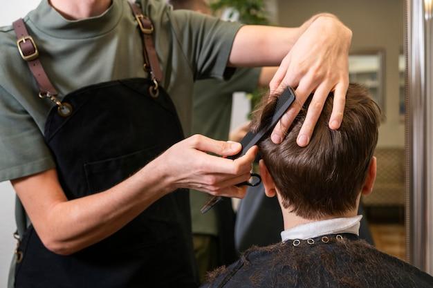 クライアントの髪を切る男
