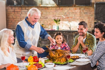 Man cutting baked chicken at table with family