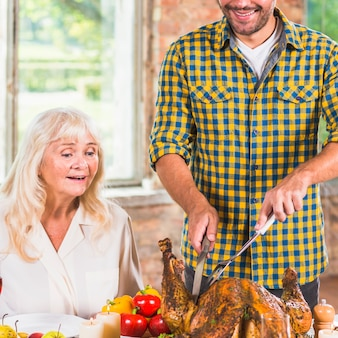 Man cutting baked chicken at table near amazed woman