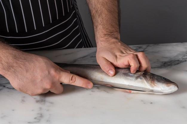 Uomo che taglia una spigola per cucinare