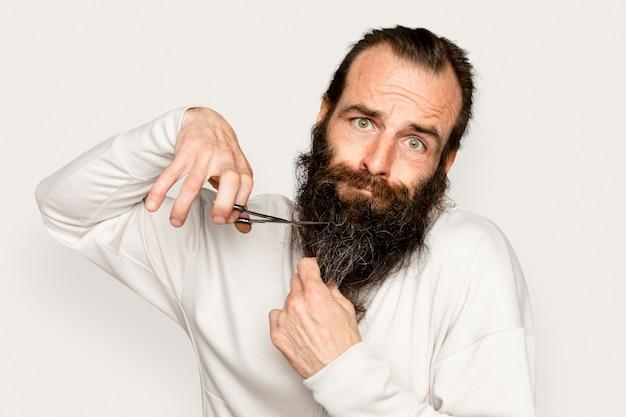 Uomo che taglia la cura della barba su sfondo bianco