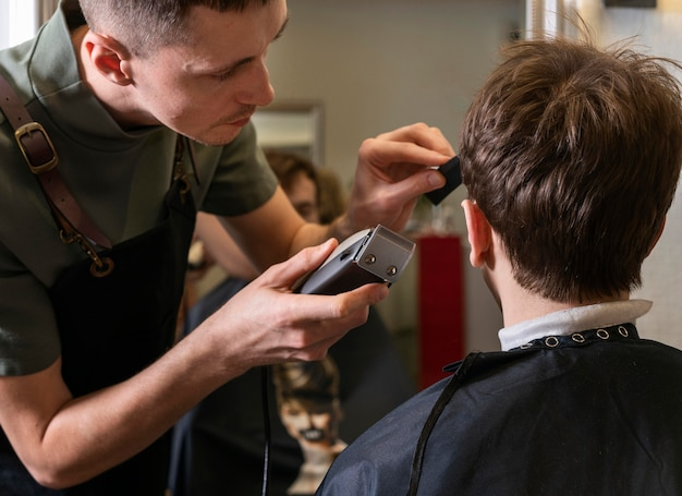 Uomo che taglia i capelli di un cliente
