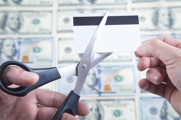 はさみでクレジットカードを切る男。