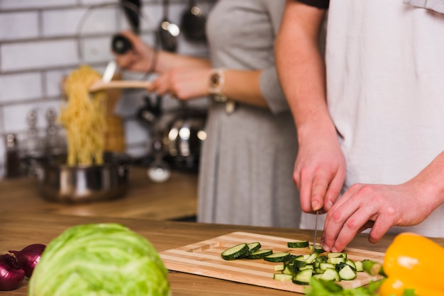 Man cutting cucumbers and woman cooking pasta