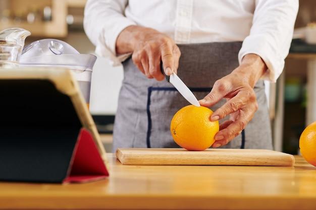 新鮮なオレンジを切る男